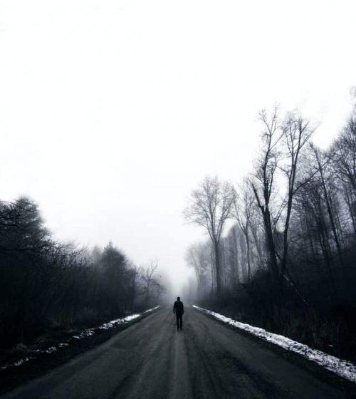 Hombre caminando solo por camino en medio de árboles