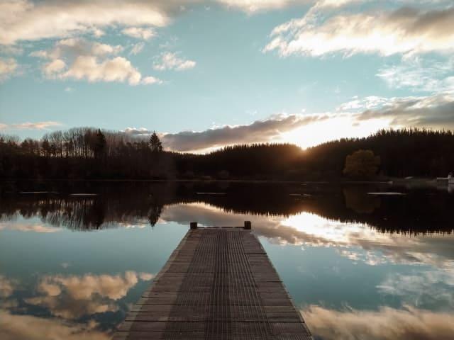 Puente de madera sobre lago con montañas delante