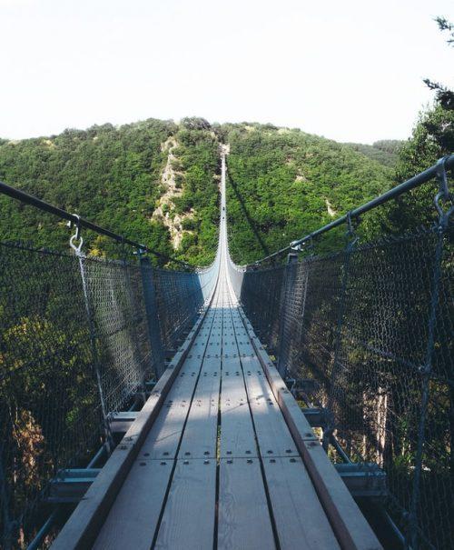 Puente colgante de madera entre montañas