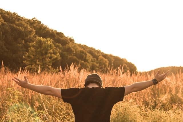 Jóven con brazos levantados en el campo