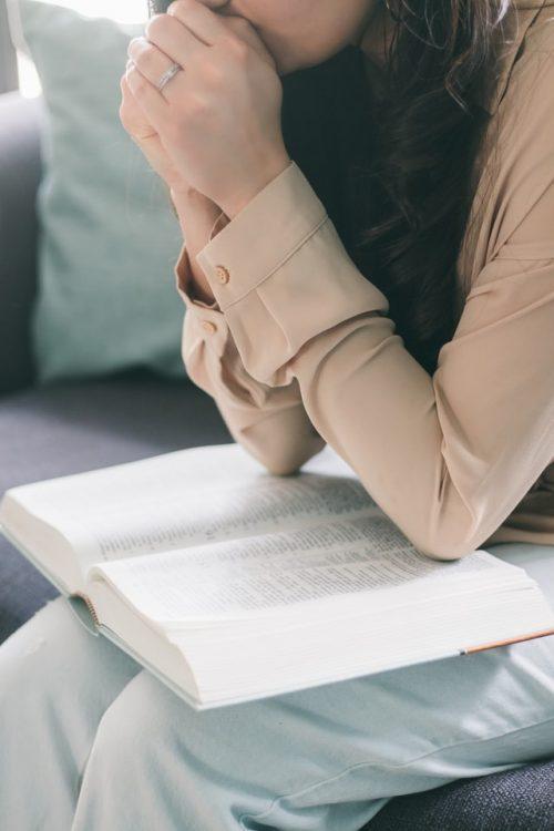 Mujer orando con la biblia