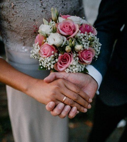 Recién casados tomados de las manos con flores